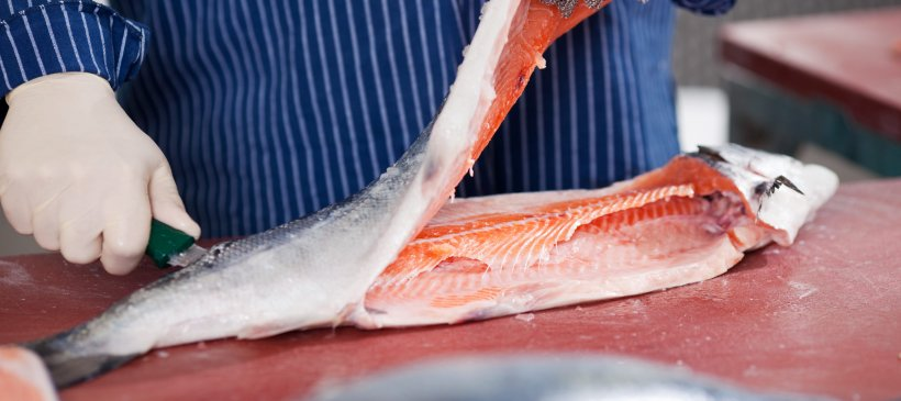 Worker cutting fish
