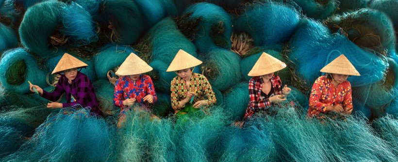 Vietnamese women are sitting repairing fishing nets